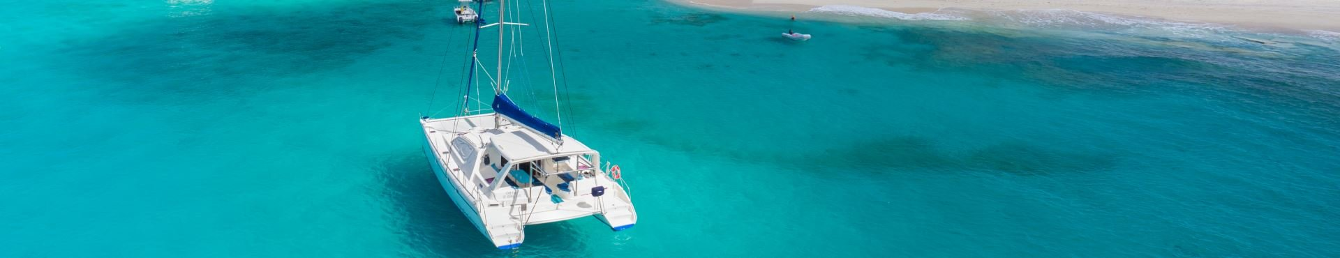 Catamaran sailing around island | Shine Lawyers