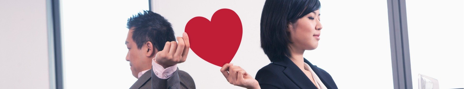 Work romance between two business people holding a heart | Shine Lawyers