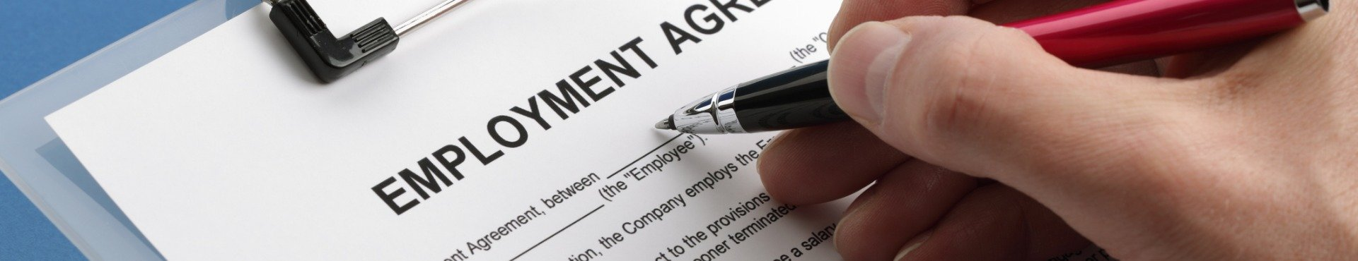 Caucasian hand filling out an employment agreement contract | Shine Lawyers